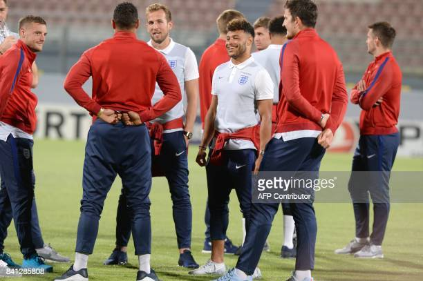 England's midfielder Alex Oxlade-Chamberlain jokes with teammates as they tour the National Stadium in Malta's Ta' Qali village, on the eve of the...
