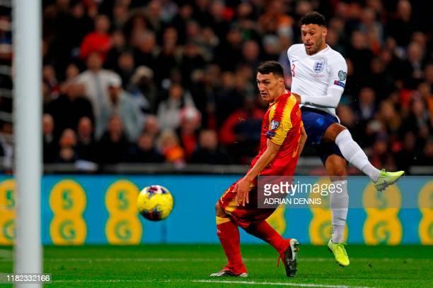 England's midfielder Alex OxladeChamberlain shoots past Montenegro's defender Risto Radunovic to score the opening goal of the UEFA Euro 2020...