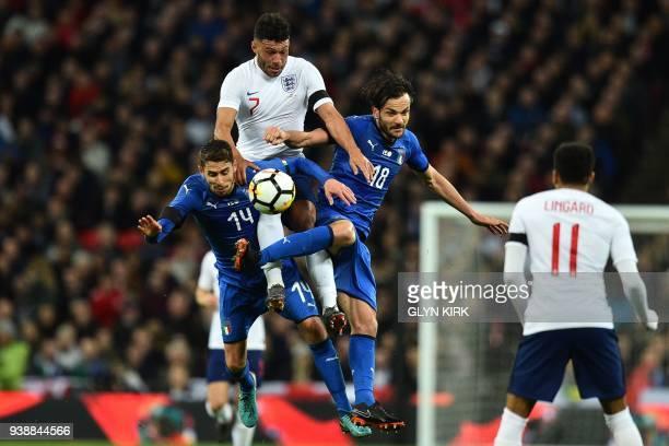 England's midfielder Alex OxladeChamberlain vies with Italy's midfielder Jorginho and Italy's midfielder Marco Parolo during the International...