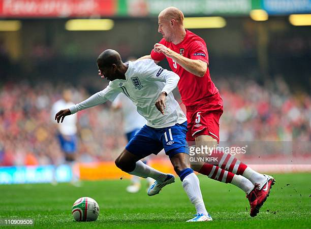 England's midfielder Ashley Young is brought down by Wales' defender James Collins resulting in a penalty during their Euro 2012 group G qualifying...