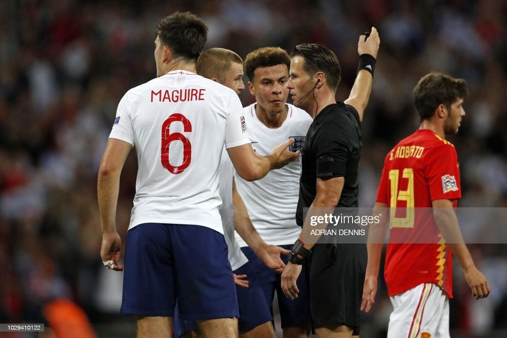England's midfielder Dele Alli (C) and England's midfielder Eric Dier (2nd L) speak with Dutch referee Danny Makkelie after he disallows a late goal by England's striker Danny Welbeck (not pictured) during the UEFA Nations League football match between England and Spain at Wembley Stadium in London on September 8, 2018. (Photo by Adrian DENNIS / AFP) / NOT