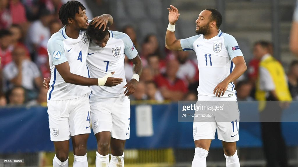 England's midfielder Demaray Grey (C) celebrate scoring the opening goal with his teamate Nathaniel Chalobach (L) and Nathan Redmond during the UEFA U-21 European Championship Group A football match England v Poland in Kielce, Poland on June 22, 2017. /