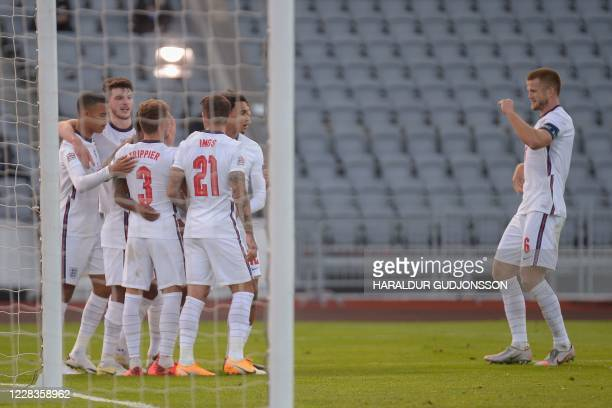 England's midfielder Eric Dier and his team-mates celebrate after England's forward Raheem Sterling scored from the penalty spot during the UEFA...
