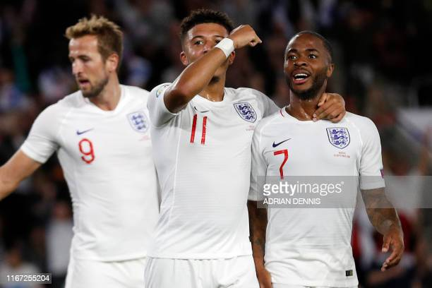England's midfielder Jadon Sancho celebrates with England's midfielder Raheem Sterling after scoring his second and the team's fifth goal during the...