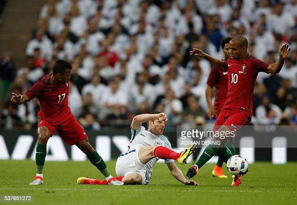 England's midfielder James Milner is tackled by Portugal's attacker Joao Eduardo during the friendly football match between England and Portugal at...