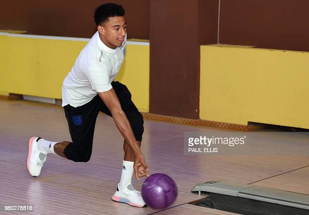 England's midfielder Jesse Lingard plays ten pin bowling at the media centre in Repino Russia on June 21 during the Russia 2018 World Cup football...