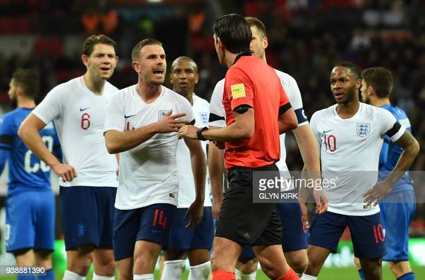 England's midfielder Jordan Henderson and other England players question the decision by German referee Deniz Aytekin to give a penalty after he...