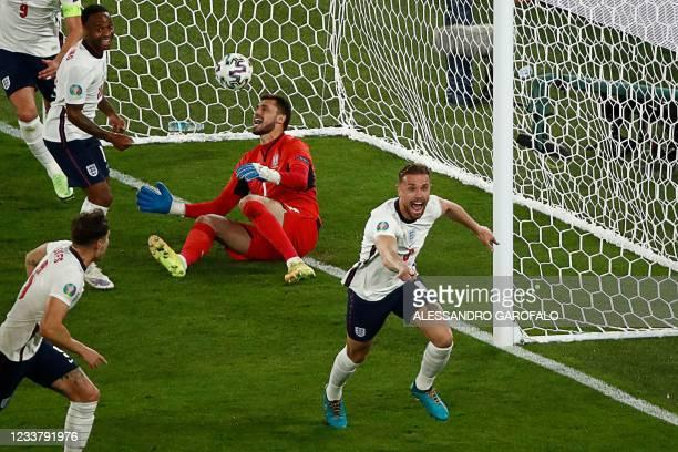 England's midfielder Jordan Henderson celebrates scoring the team's fourth goal during the UEFA EURO 2020 quarter-final football match between...