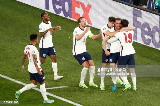 England's midfielder Jordan Henderson celebrates with teammates after scoring the team's fourth goal during the UEFA EURO 2020 quarter-final football...