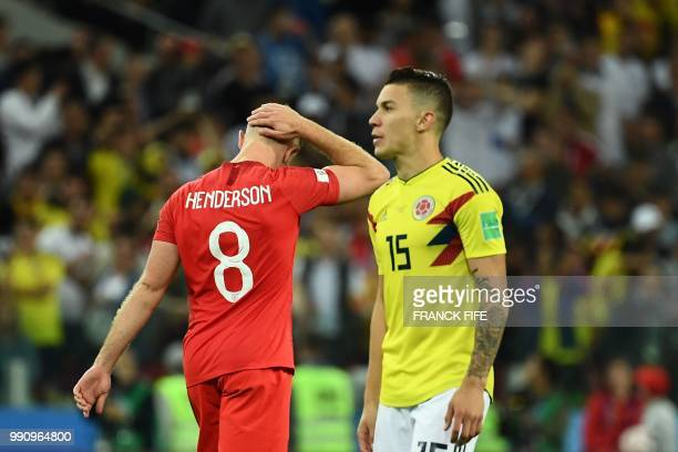 England's midfielder Jordan Henderson reacts after missing a penalty as Colombia's midfielder Mateus Uribe prepares for his penalty kick during the...
