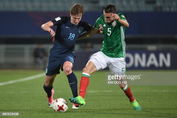 England's midfielder Kieran Dowell and Mexico's defender Manuel Mayorga compete for the ball during the U20 World Cup quarterfinal football match...