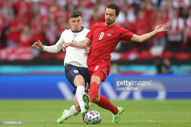 England's midfielder Mason Mount fights for the ball with Denmark's midfielder Thomas Delaney during the UEFA EURO 2020 semi-final football match...