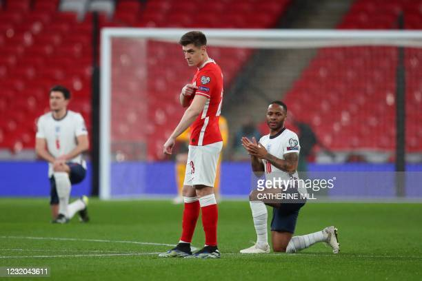 England's midfielder Raheem Sterling and the England players take a knee against racism as Poland's forward Krzysztof Piatek points to his 'respect'...