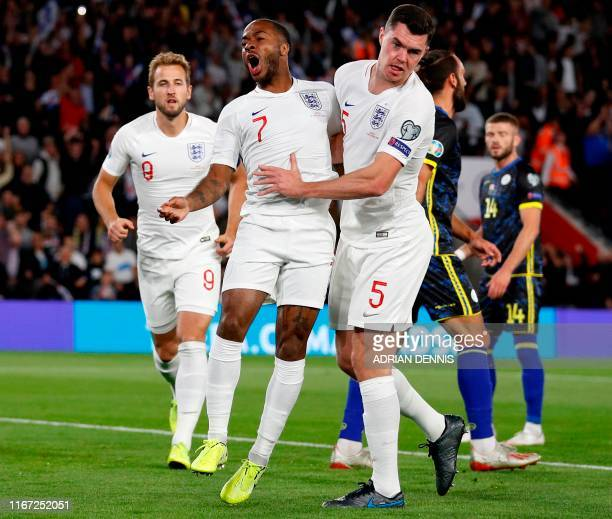 England's midfielder Raheem Sterling celebrates with England's defender Michael Keane after scoring the equalising goal during the UEFA Euro 2020...