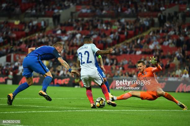 England's midfielder Raheem Sterling is closed down by Slovakia's goalkeeper Martin Dubravka and Slovakia's defender Jan Durica during the World Cup...