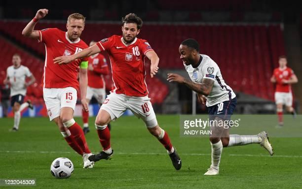 England's midfielder Raheem Sterling takes on Poland's defender Kamil Glik and Poland's defender Bartosz Bereszynski during the FIFA World Cup Qatar...