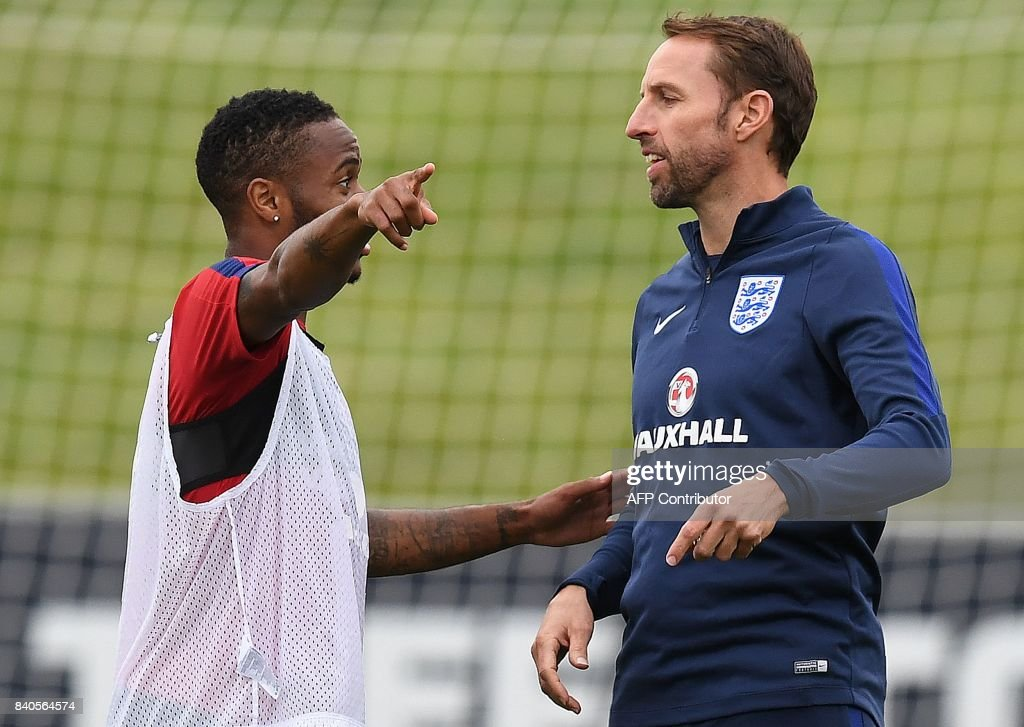 England's midfielder Raheem Sterling (L) talks with England's manager Gareth Southgate during a training session at St George's Park in Burton-on-Trent on August 29, 2017, as part of an England football team media day ahead of their 2018 FIFA World Cup qualifier matches against Malta on September 1 and Slovakia on September 4. / AFP PHOTO / Paul ELLIS / NOT