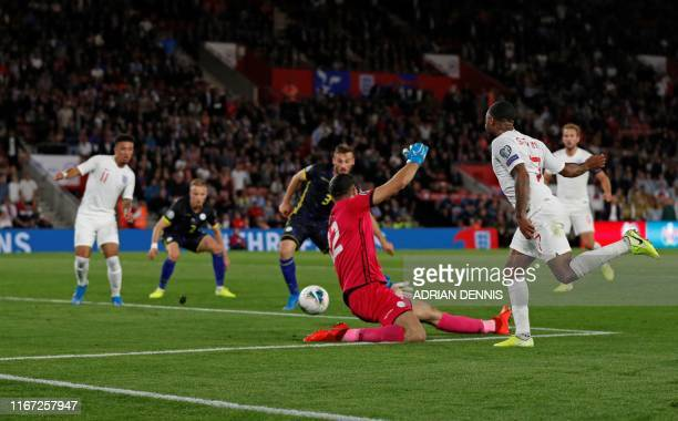 England's midfielder Raheem Sterling watches his cross to England's midfielder Jadon Sancho who went on to score his second and the team's fifth goal...