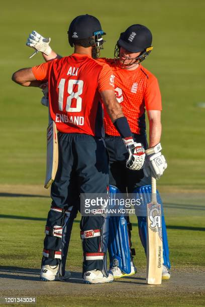 England's Moeen Ali and captain Eoin Morgan celebrate after winning the third T20 International cricket match between South Africa and England at the...