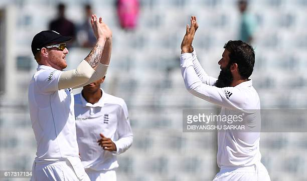 England's Moeen Ali and teammate Ben Stokes celebrate the wicket of Bangladesh Tamim Iqbal during the fourth day of the first Test match between...