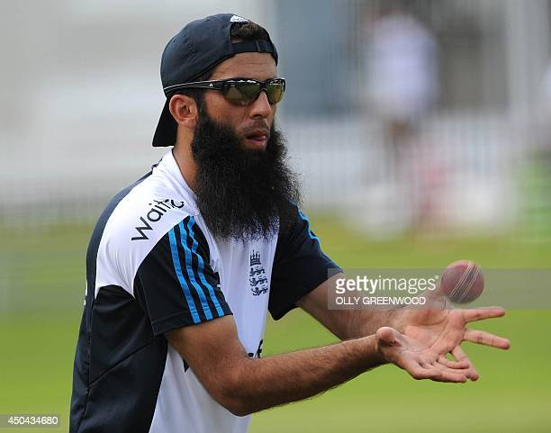 England's Moeen Ali catches the ball during a practice session at Lords cricket ground in London on June 11, 2014 ahead of the first Test match...