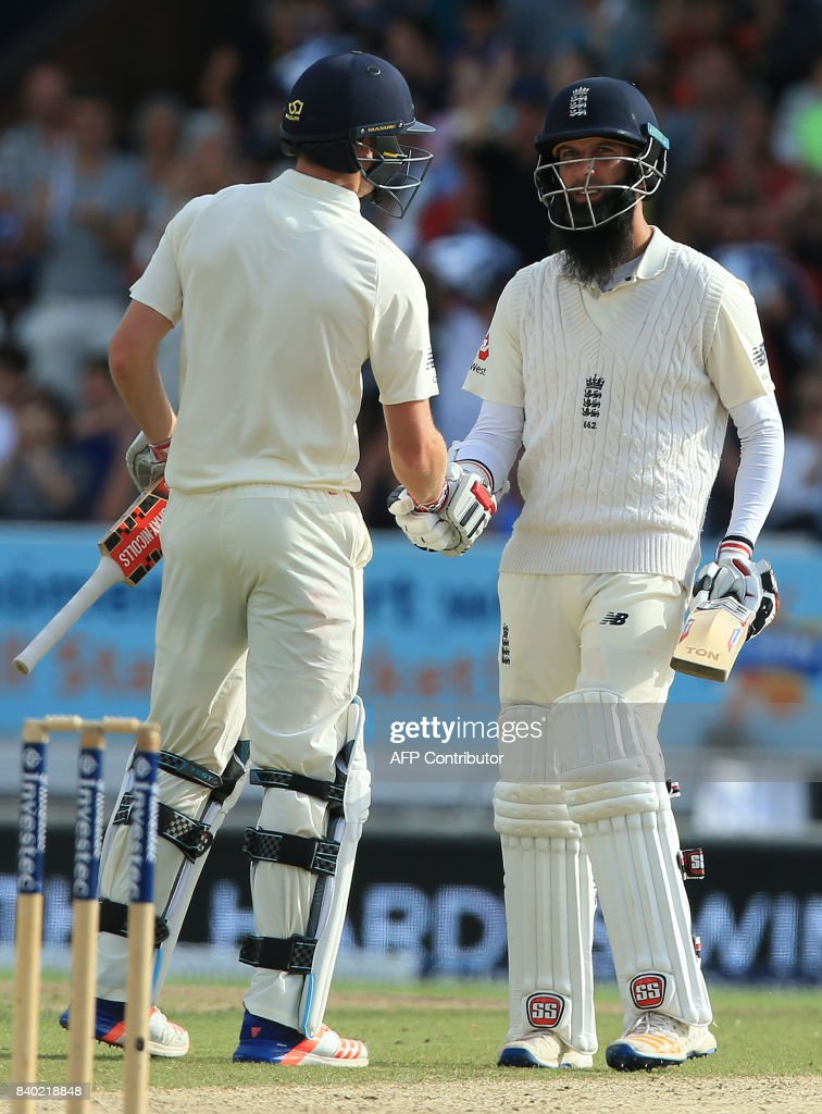 England's Moeen Ali celebrates his half century with England's Chris Woakes on the fourth day of the second international Test match between England and the West Indies at Headingley cricket ground in Leeds, northern England, August 28, 2017. / AFP PHOTO / Lindsey Parnaby / RESTRICTED