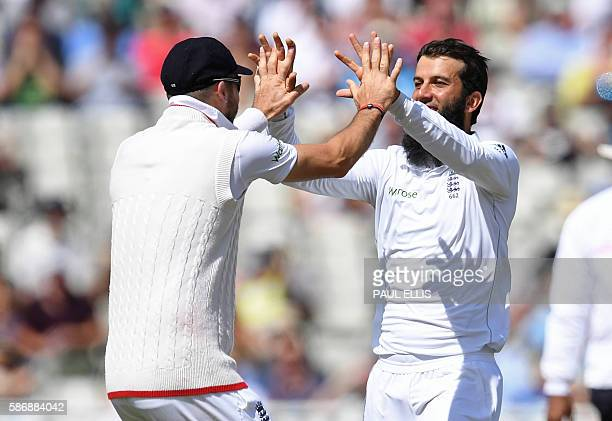 England's Moeen Ali celebrates with England's James Anderson after taking the wicket of Pakistan's Azhar Ali during play on the final day of the...