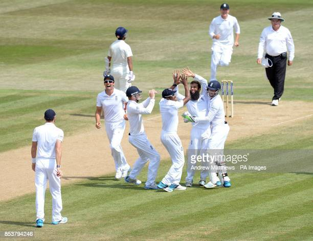 England's Moeen Ali is congratulated by his team mates after taking the wicket of India's Bhuvneshwar Kumar during day five of the Third Investec...