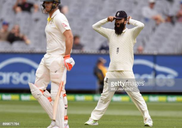 England's Moeen Ali yawns as Australia's batsman Mitchell Marsh walks past on the final day of the fourth Ashes cricket Test match at the MCG in...