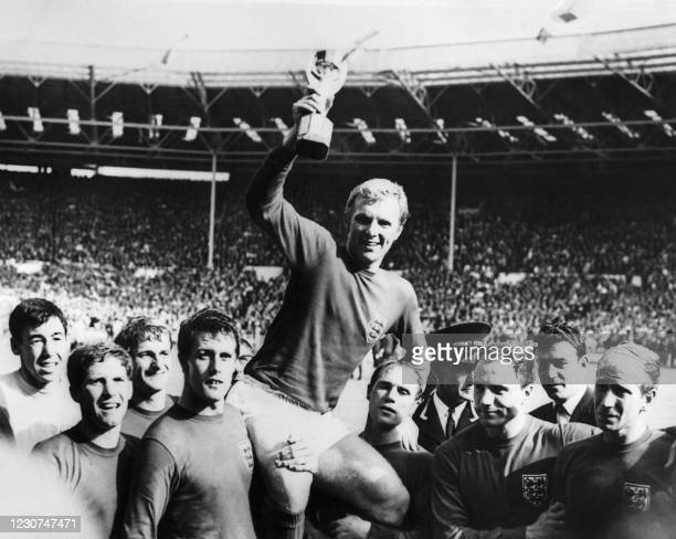 England's national soccer team captain Bobby Moore holds aloft the Jules Rimet trophy as he is carried by his teammates following England's victory...