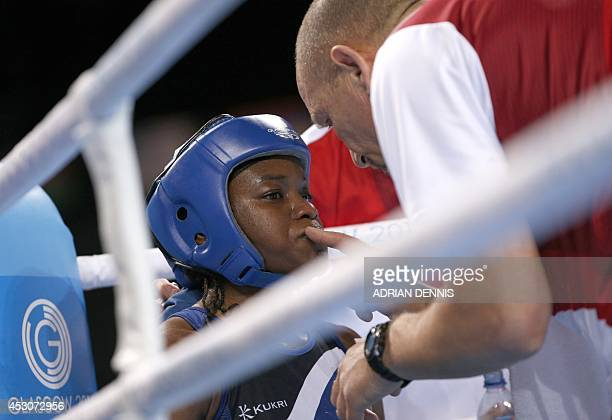 England's Nicola Adams gets vasaline applied to her lips by a cornerman during her women's fly final boxing match against Northern Ireland's Michaela...