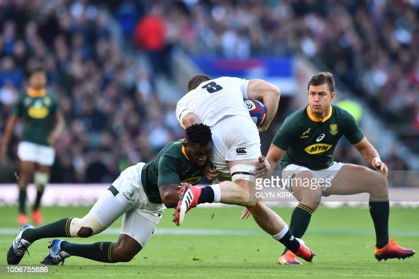 England's number 8 Mark Wilson is tackled by South Africa's flanker Siya Kolisi during the international rugby union test match between England and...