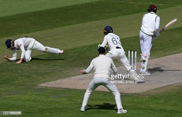 England's Ollie Pope dives to catch the ball to take the wicket of West Indies' Alzarri Joseph for 32 runs on the fourth day of the second Test...