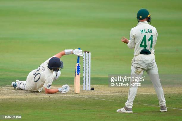 England's Ollie Pope falls inside the crease after ducking for a bouncer ball as South Africa's Pieter Malan looks on during the first day of the...