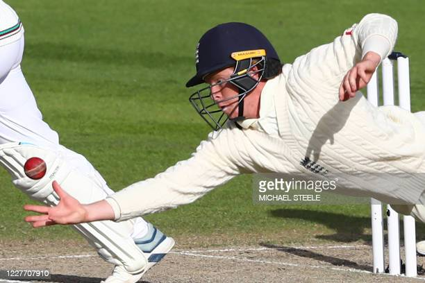 England's Ollie Pope stretches out to make a catch to dismiss West Indies' Kemar Roach off the bowling of England's Dom Bess, the final wicket as...