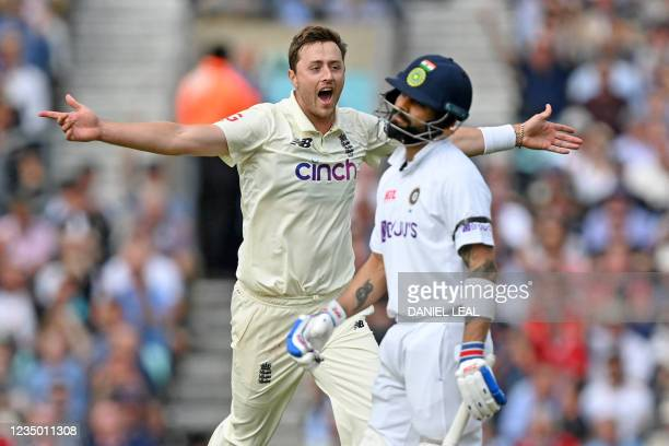 England's Ollie Robinson celebrates after taking the wicket of India's captain Virat Kohli for 50 runs during play on the first day of the fourth...