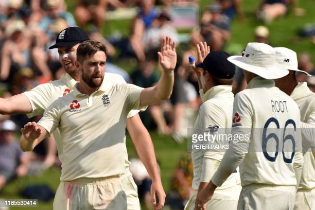 England's paceman Chris Woakes celebrates his wicket of New Zealand's batsman Tim Southee with teammates on day two of the second cricket Test match...