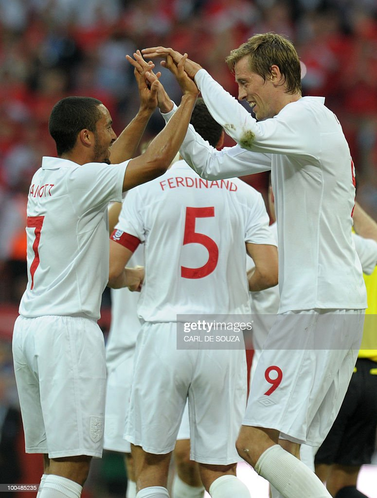 England's Peter Crouch (R) celebrates with Theo Walcott after scoring his goal against Mexico during their international friendly football match at Wembley Stadium in London on May 24, 2010 AFP PHOTO/Carl de Souza
