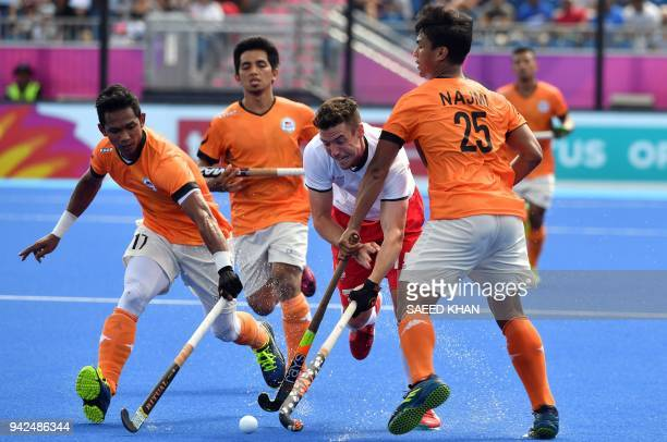 England's Phillip Roper vies for the ball with Malaysia's Razie Rahim and Najmi Jazlan during their men's field hockey match at the 2018 Gold Coast...