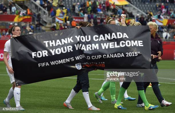 England's players carry a banner thanking the host country at the end of a Group F match at the 2015 FIFA Women's World Cup between France and...