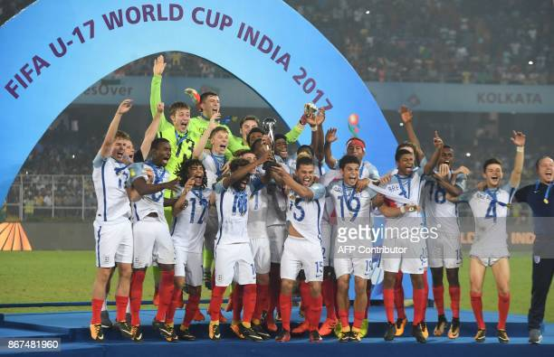England's players celebrate with their trophy after winning the final FIFA U17 World Cup football match against Spain at the Vivekananda Yuba Bharati...