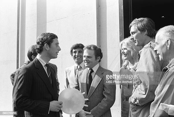 England's Prince Charles holds an inflated surgical glove and chats with members of the cast of M*A*S*H during a visit to the set of the show October...