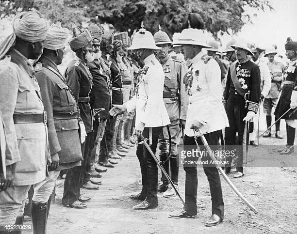 England's Prince of Wales while reviewing veterans of the Indian Army leans forward to reverntly touch the sword hilt of a famous old Indian warrior...