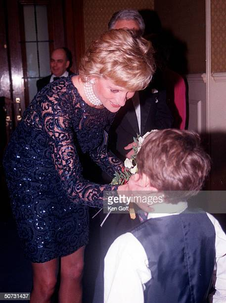 England's Princess Diana in short black lacey dress thanking a young boy for the flowers he presented to her at a charity event at the Royal Albert...