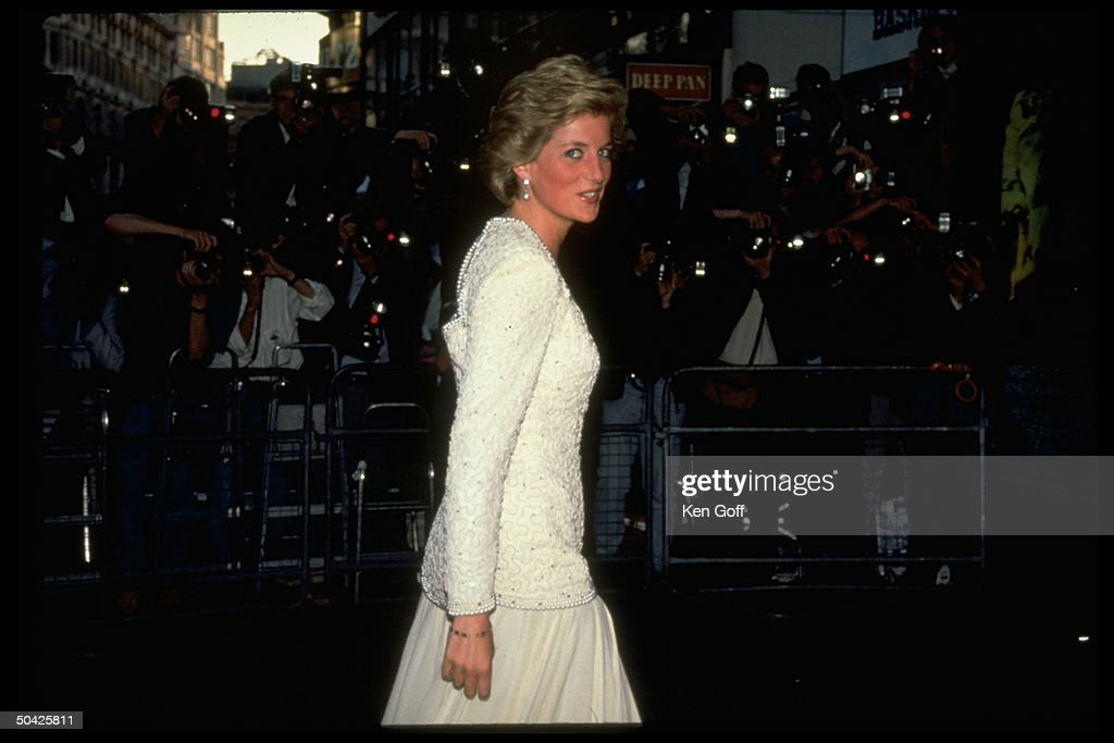 England's Princess Diana, wearing white beaded top & skirt, at royal premiere of Back to the Future III w. row of photographers in bkgrd., England.