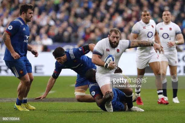 England's prop Joe Marler is is tackled by France's flanker Kelian Galletier and France's flanker Yacouba Camara during the Six Nations international...