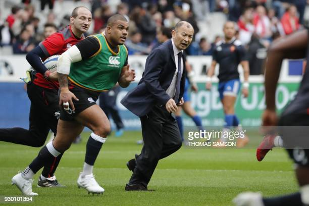 England's prop Kyle Sinckler and England's head caoch Eddie Jones run during warm up prior to the Six Nations international rugby union match between...