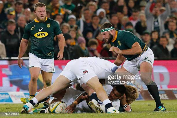 England's prop Mako Vunipola protects the ball while in a ruck as South Africa's tight head prop Thomas du Toit and South Africa hooker Akker van der...