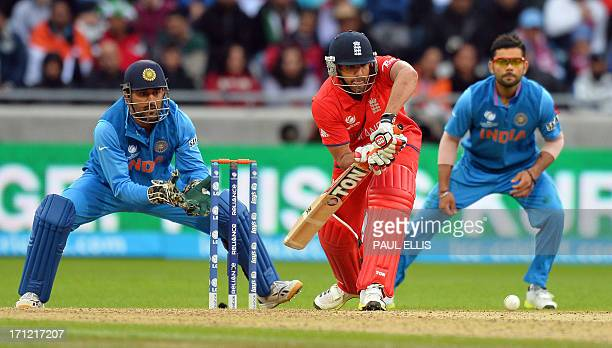 England's Ravi Bopara plays a shot as Indian captain Mahendra Singh Dhoni and India's Virat Kohli look on during the 2013 ICC Champions Trophy Final...