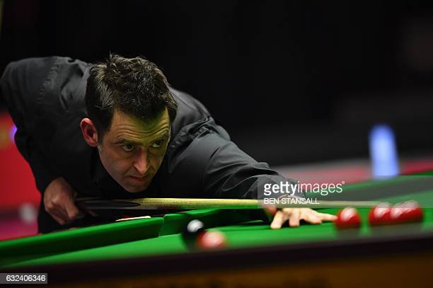 England's Ronnie O'Sullivan plays a shot during the final of the Masters snooker tournament against England's Joe Perry at Alexandra Palace in London...